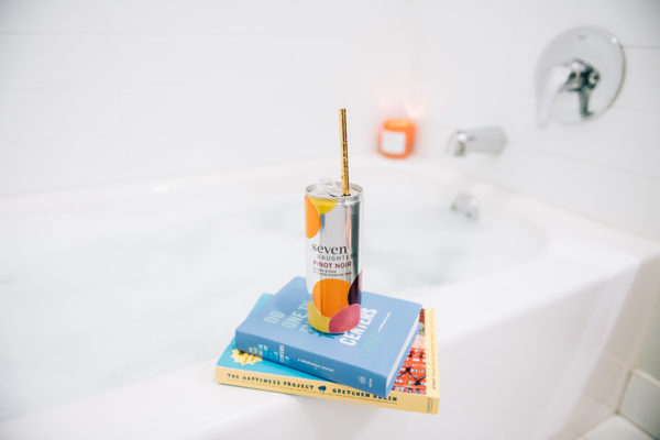 Seven Daughters Pinot Noir can in the bathtub with books and a candle.