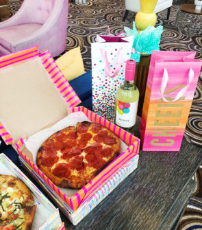 Jessica Sturdy hosts a pink-themed pizza party in Chicago with rosé, Happy Camper pizza, and colorful pizza boxes covered in wrapping paper.