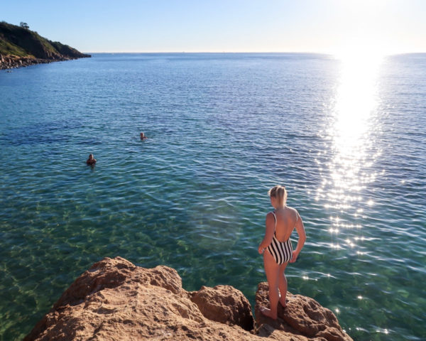 Jessica Sturdy wearing a black and white one piece swimsuit from J.Crew cliffjumping on the Mornington Pensinula in Australia near Melbourne