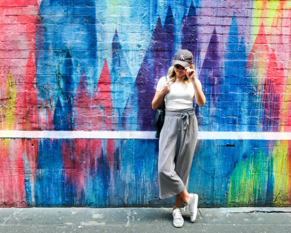 Jessica Sturdy wearing gingham pants, yankees hat, and gingham sneakers in front of wall art in Melbourne Australia