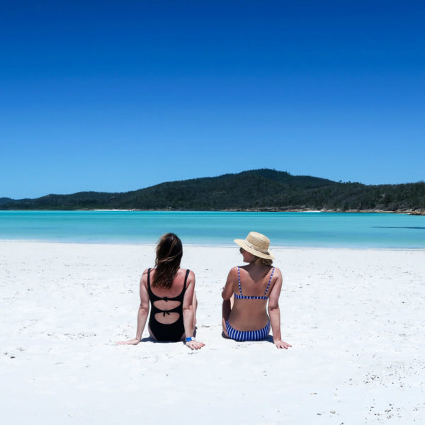 Hallie Wilson and Jessica Sturdy wearing swimsuits on Whitehaven Beach in the Whitsundays in Australia