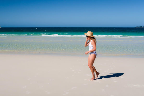 Jessica Sturdy wearing a Heidi Klein striped one piece swimsuit on Whitehaven Beach in the Whitsundays in Australia