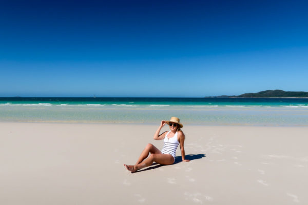 Jessica Sturdy wearing a striped one piece swimsuit on Whitehaven Beach in the Whitsundays in Australia