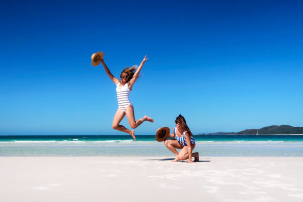 Jessica Sturdy and Hallie Wilson wearing striped swimsuits on Whitehaven Beach in the Whitsundays Islands in Australia
