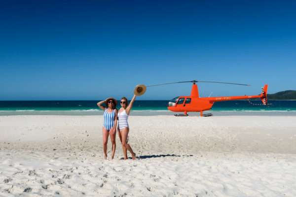 Hallie Wilson and Jessica Sturdy wearing striped one piece swimsuits in front of an orange helicopter on Whitehaven Beach in the Whitsundays in Australia