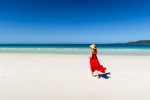 Jessica Sturdy on Whitehaven Beach in the Whitsundays in Australia wearing a ruffled red maxi dress.