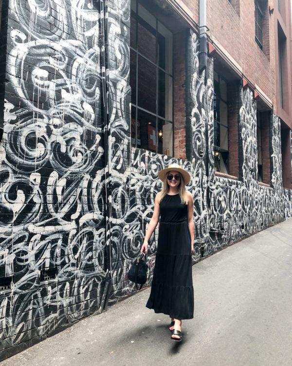 Jessica Sturdy wearing a black maxi dress in front of street art in Melbourne Australia