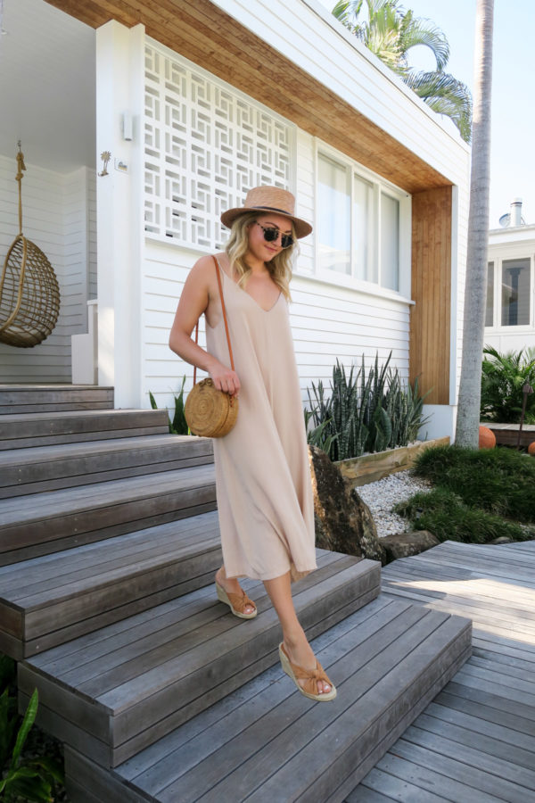 Jessica Sturdy wearing a long flowy jumpsuit and wicker bag at Bask & Stow in Byron Bay Australia