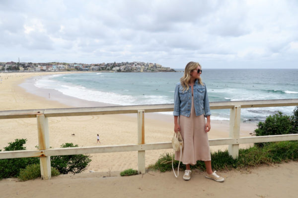 Jessica Sturdy wearing a denim jacket, jumpsuit, and sneakers in Bondi Beach in Sydney Australia