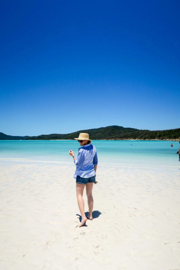 Jessica Sturdy on Whitehaven Beach in the Whitsundays in Australia wearing a Vineyard Vines striped shirt and jean shorts.