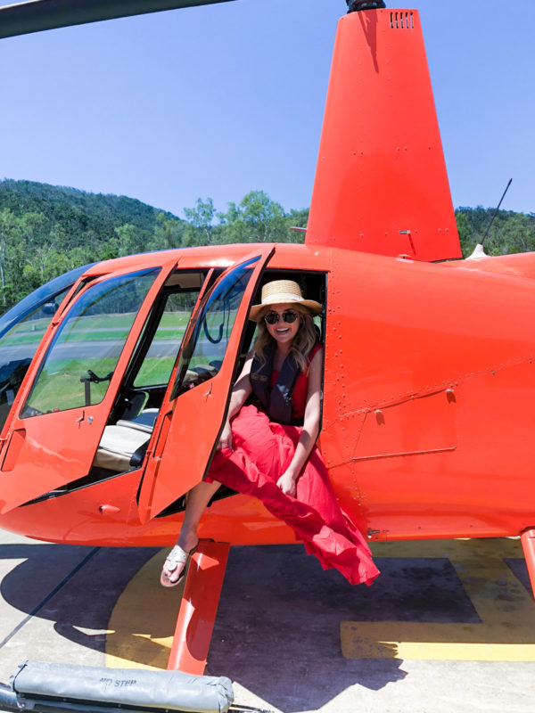Jessica Sturdy wearing a red maxi dress in an orange helicopter in the Whitsundays in Australia
