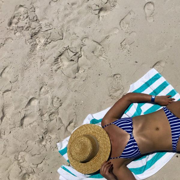 Jessica Sturdy wearing a striped J.Crew bikini and a straw hat on Whitehaven Beach in Australia