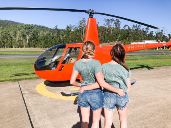 Jessica Sturdy and Hallie Wilson wearing partners in crime tee shirts in front of an orange helicopter in Australia