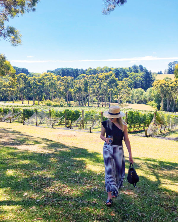 Jessica Sturdy wearing a black one shoulder top with striped wide leg pants at a winery on Mornington Peninsula outside of Melbourne Australia