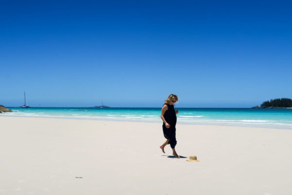 Jessica Sturdy on Whitehaven Beach in the Whitsundays in Australia wearing a navy blue maxi dress.