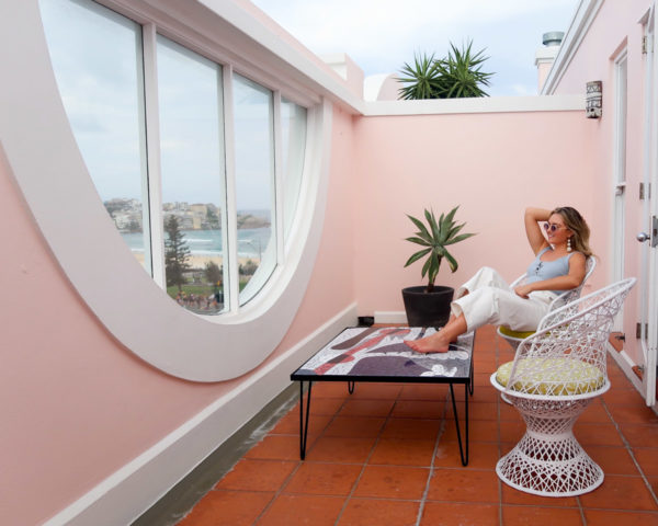 Jessica Sturdy wearing white cropped jeans and a blue bodysuit on a pink balcony at Hotel Ravesis on Bondi Beach in Sydney Austalia