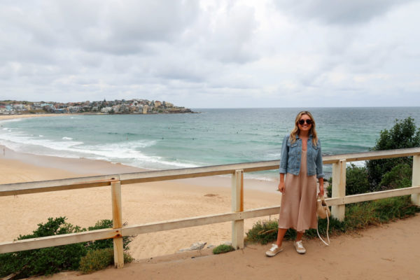 Jessica Sturdy wearing a denim jacket, sneakers, and a tan jumpsuit in front of Bondi Beach in Austalia