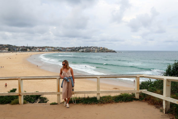 Jessica Sturdy wearing a tan jumpsuit, Superga sneakers, and a denim jacket in Bondi Beach in Sydney Australia