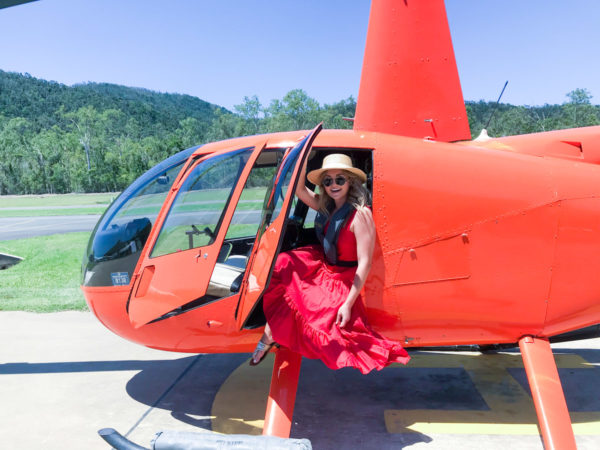 Jessica Sturdy wearing a ruffled red maxi dress inside of an orange helicopter in Airlie Beach Australia