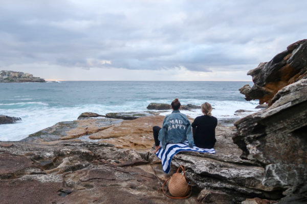 Hallie Wilson and Jessica Sturdy on a rock waiting for sunset in Bondi Beach Australia. Hallie is wearing a Mad Happy jean jacket.