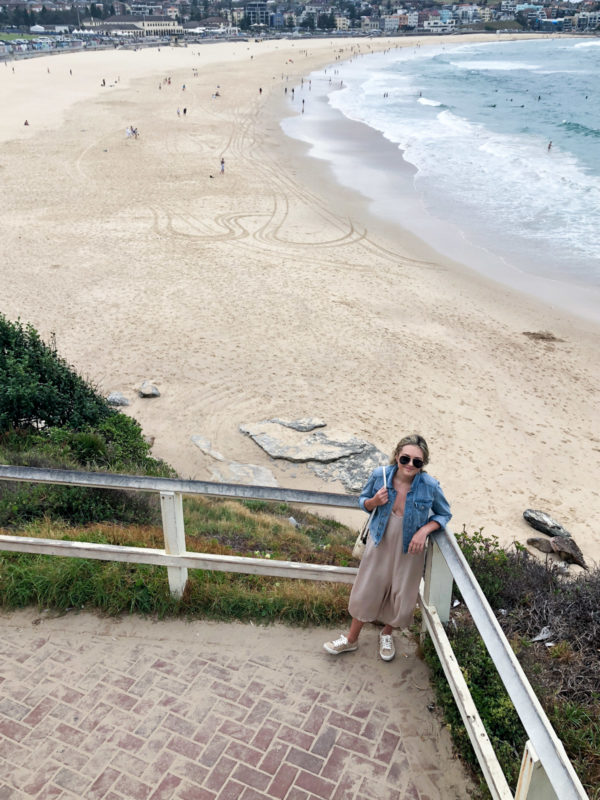Jessica Sturdy wearing a jean jacket and jumpsuit with sneakers in Bondi Beach Australia