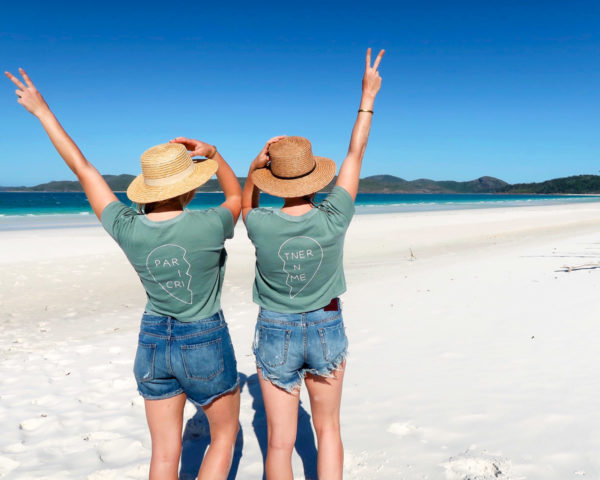 Jessica Sturdy and Hallie Wilson wearing Partners in Crime tee shirts, jean shorts, and straw hats on Whitehaven Beach on the Whitsunday Islands in Australia