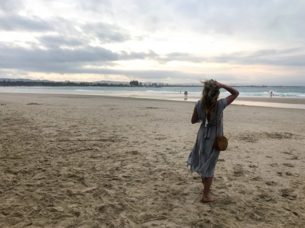 Jessica Sturdy wearing a blue and white striped dress on the beach in Byron Bay Australia