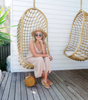 Jessica Sturdy wearing a jumpsuit and a straw hat in a swinging rattan chair at Bask & Stow in Byron Bay in Australia