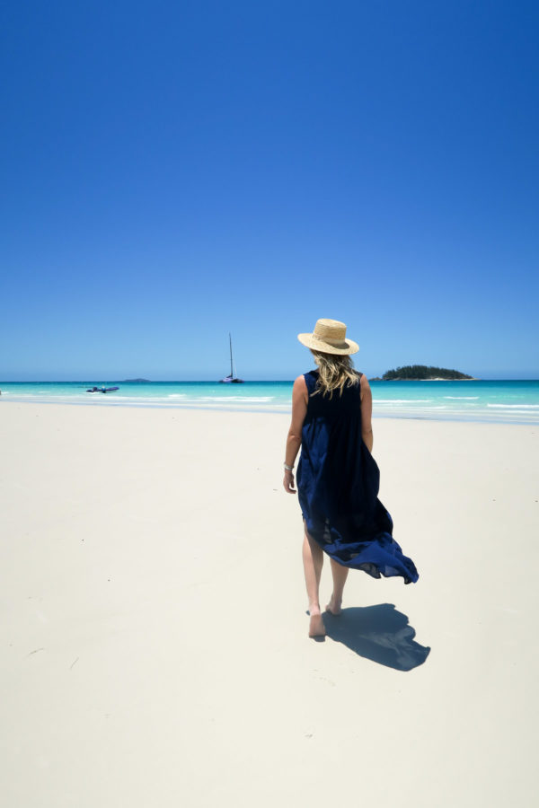 Jessica Sturdy on Whitehaven Beach in the Whitsundays in Australia wearing a Vineyard Vines dress and straw hat.