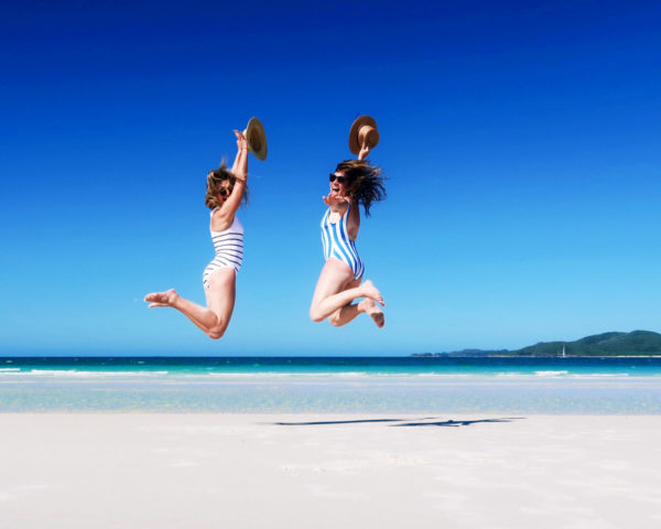 Jessica Sturdy and Hallie Wilson in striped one piece swimsuits on Whitehaven Beach in the Whitsundays in Australia