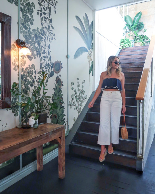Jessica Sturdy wearing a navy blue crop top and white wide leg jeans at The Butler restaurant in Sydney Australia