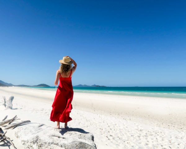 Jessica Sturdy on Whitehaven Beach in the Whitsundays in Australia wearing a red maxi dress and a straw hat.