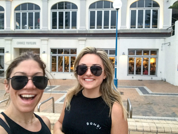 Hallie Wilson and Jessica Sturdy wearing black sunglasses outside of Coogee Pavilion in Australia