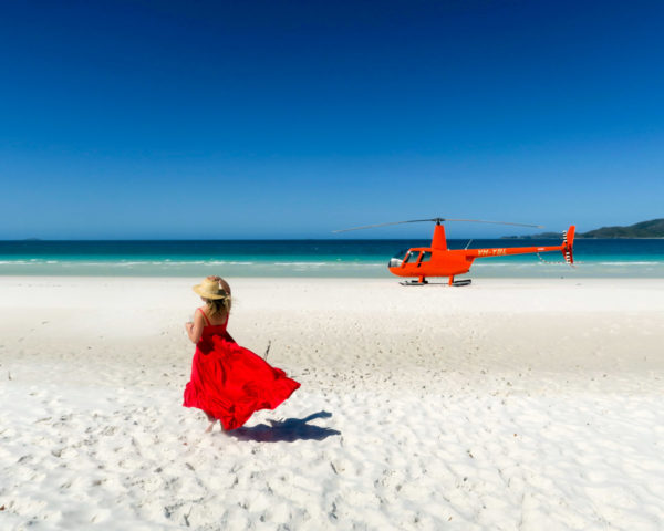 Jessica Sturdy on Whitehaven Beach in the Whitsundays in Australia wearing a red maxi dress in front of an orange helicopter.