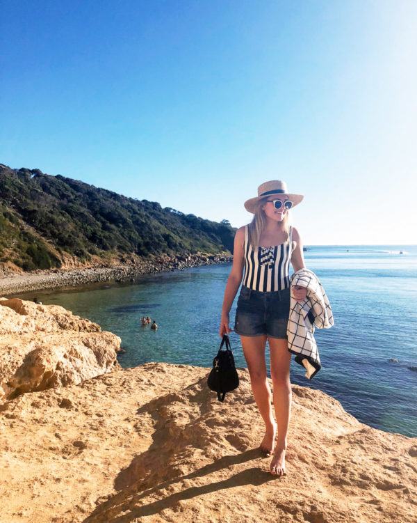 Jessica Sturdy wearing a J.Crew striped swimsuit with jean shorts on a rock cliff overlooking the ocean on the Mornington Peninsula outside of Melbourne Australia