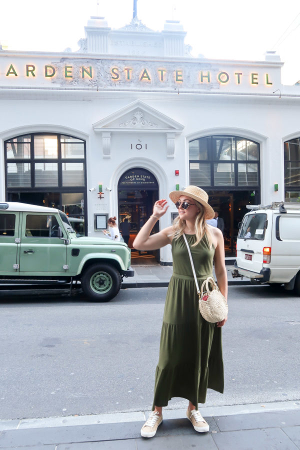 Jessica Sturdy wearing a green maxi dress and Clare V straw bag in front of Garden State Hotel bar in Melbourne Australia