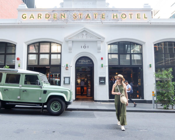 Jessica Sturdy wearing an olive green maxi dress, sneakers, and a straw hat in front of Garden State Hotel in the CBD in Melbourne Australia