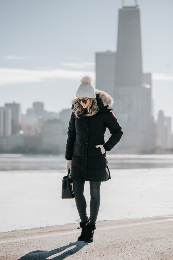 Jessica Sturdy shares tips for surviving winter in Chicago, wearing a pom beanie, Canada Goose coat, fur booties, and a Polene top handle bag.