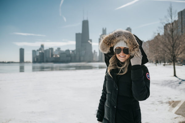 Jessica Sturdy wearing a fur-trimmed, hooded Canada Goose jacket with a pom beanie and matte aviators.