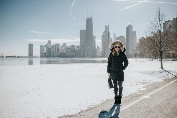Jessica Sturdy wearing a fur-trimmed, hooded Canada Goose jacket with a pom beanie, matte aviators, booties, and a Polene top handle bag by Lake Michigan.