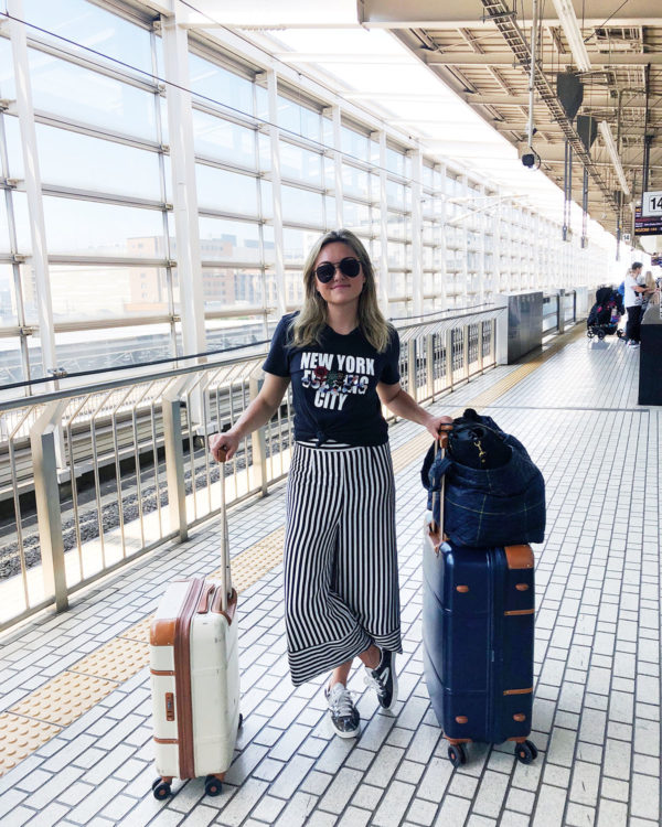Jessica Sturdy at a train station in Japan wearing a cute travel outfit: New York City tee by Cynthia Rowley, Lovers + Friends striped wide leg pants from Revolve, Bric's Bellagio Spinner Suitcases, an MZ Wallace large metro tote, Le Specs matte black aviators, and Tretorn sequins sneakers.