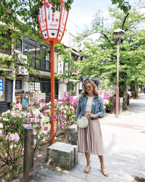 Bows & Sequins Travel Guide in Kyoto Japan. Jessica Sturdy is wearing a denim jacket, pink pleated midi skirt, a Brahmin circle handbag, and Loeffler Randall Saskia sandals.