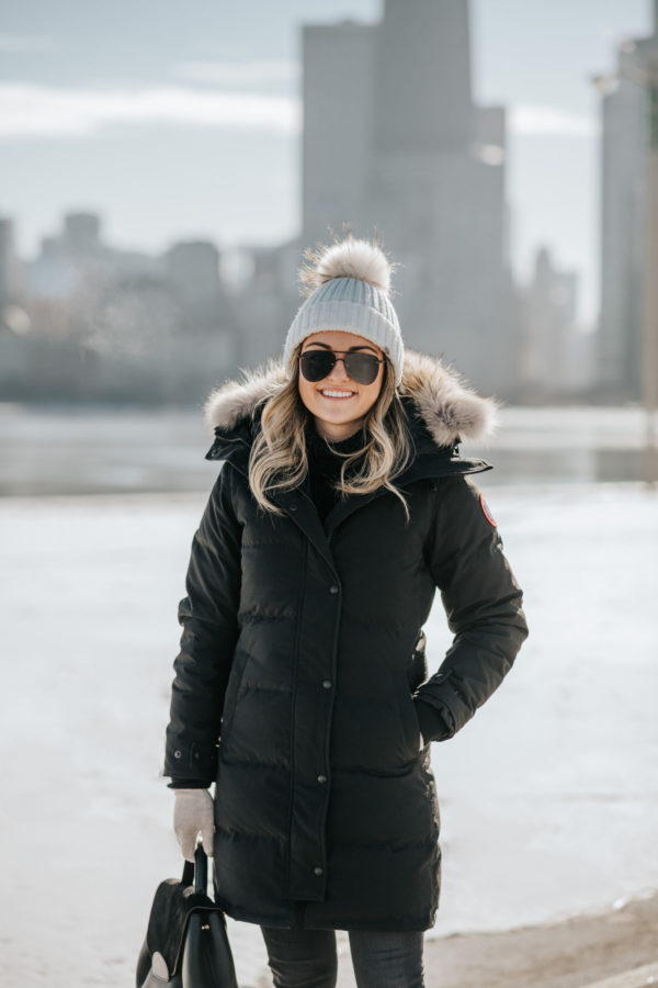 Jessica Sturdy wearing a fur-trimmed, hooded Canada Goose jacket with a pom beanie, matte aviators, and a Polene top handle bag.