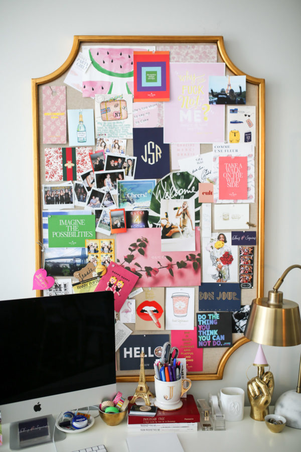 The gold memo board is from PB Teen, the blue chair with a bow is from Society Social, and the white desk is from Bungalow 5. Styled with a Gucci bag, palm leaf pillow, lucite chair, and Ikea shelves.