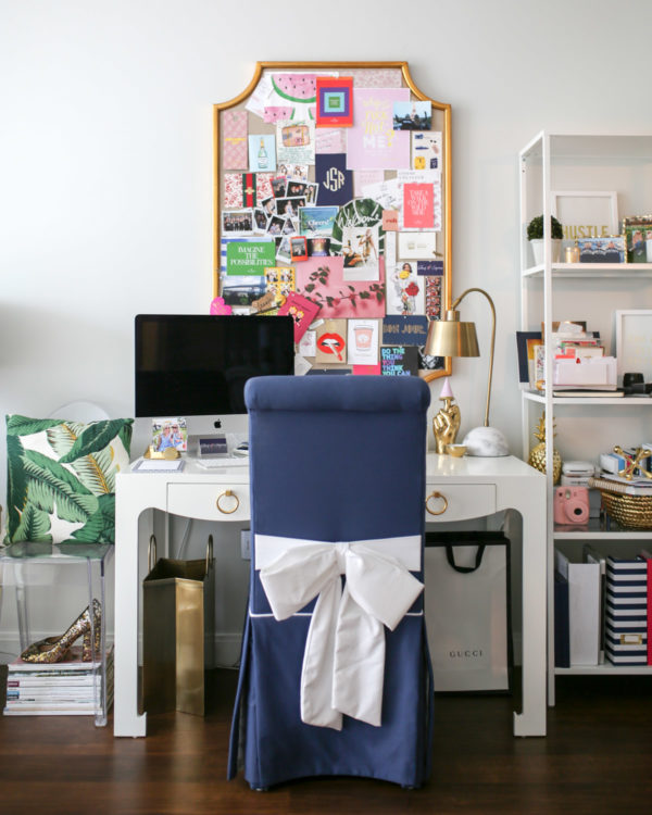 Jessica Sturdy shares photos of her colorful home office in Chicago. Bungalow 5 Desk, Society Social Navy Blue Chair with a Bow, Gucci Bag, Lucite Chair with Palm Leaf Pillow, Ikea Shelves, gold shopping bag trash can, and an Apple iMac desktop computer.