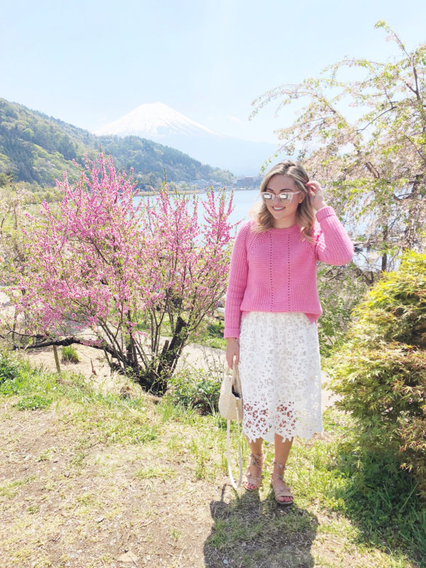 Bows & Sequins Travel Guide in Mt Fuji Five Lakes Japan. Jessica Sturdy is wearing a pink J.Crew sweater, a white lace skirt by Ann Taylor, a Clare V Petit Alice Straw Tote, and Loeffler Randall pom pom sandals.