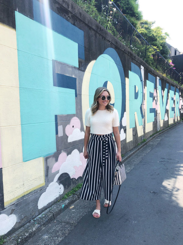 Bows & Sequins Travel Guide in Tokyo Japan. Jessica Sturdy in front of the Now is Forever street art mural in Omotesando wearing a cropped short-sleeve sweater, cropped wide leg striped pants, Soludos knotted slides, and a Clare V striped tote bag.