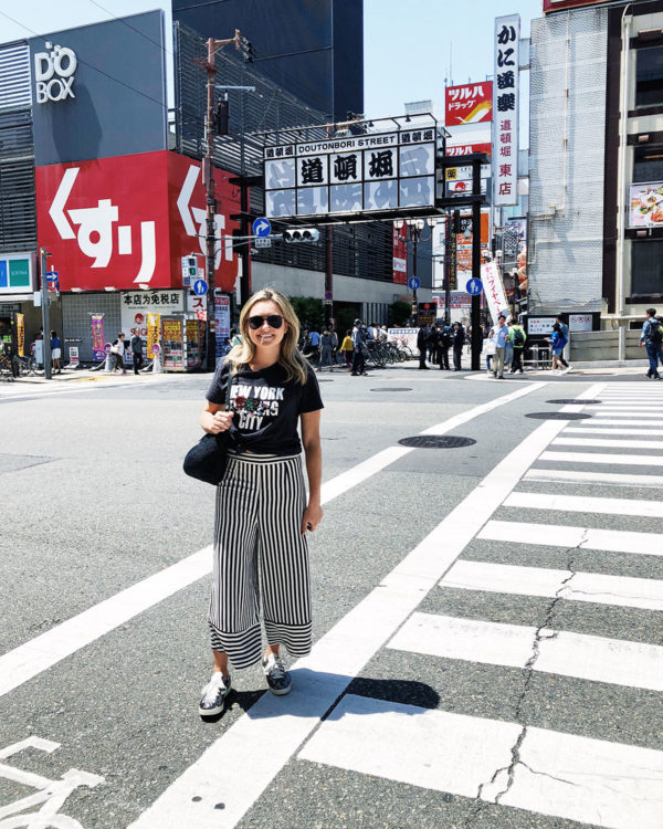 Jessica Sturdy in Osaka Japan near Doutonbori Street wearing a Cynthia Rowley New York City Tee with Lovers + Friends striped wide leg cropped pants and Tretorn sequin sneakers.