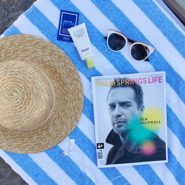 Jessica Sturdy shares a poolside photo from the Miramonte Resort in Indian Wells with a Palm Springs Life Magazine, blue striped towel, L*Space straw hat, Supergoop Unseen sunscreen, and white sunglasses.