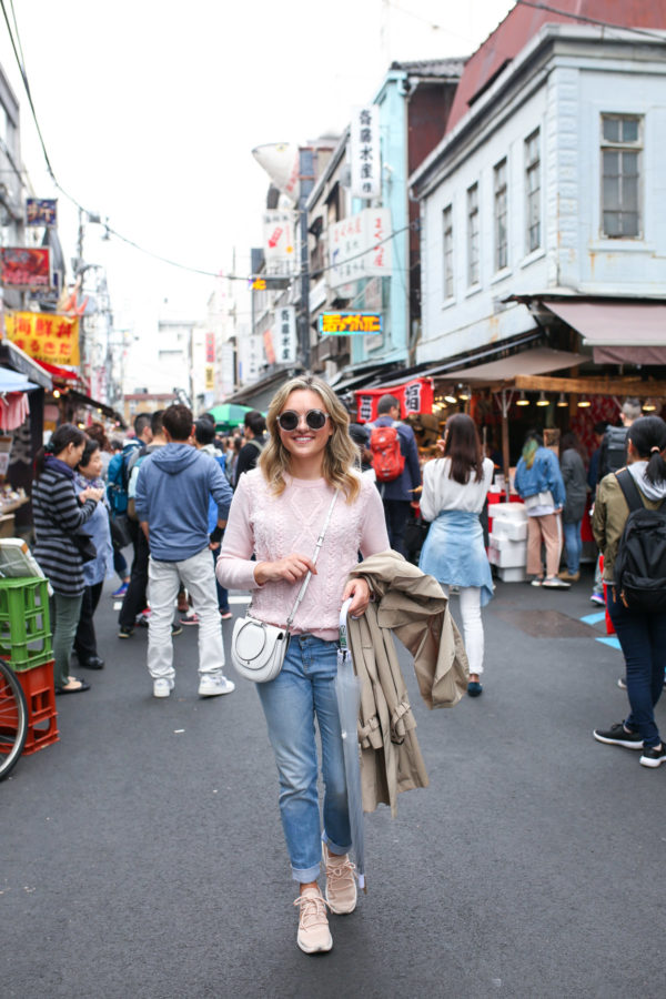 Travel blogger Jessica Sturdy styling a pink J.Crew sweater with boyfriend jeans and sneakers while traveling in Japan.
